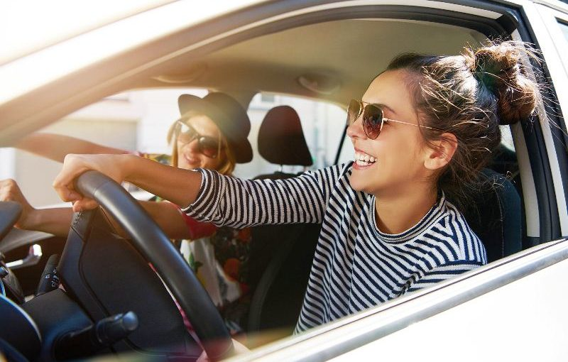 Two fun young women in sunglasses driving in a car in town laughing and smiling as they socialise together, view through open side window; Shutterstock ID 608752922; Jobnummer: -